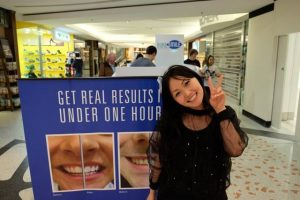 Teeth Whitening - Kouture Kitty posing next to before and after tarpaulin
